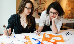 Maria Doering and Fiona Chinkan work on a drawing